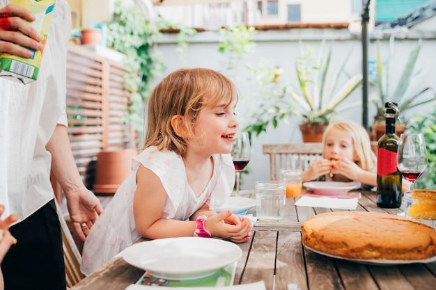 自家製ケーキを食べる女児屋外座っているテーブル