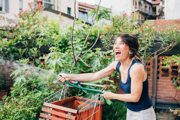 ミッドアダルト女性屋外テラスガーデニング水やり植物笑って楽しんで