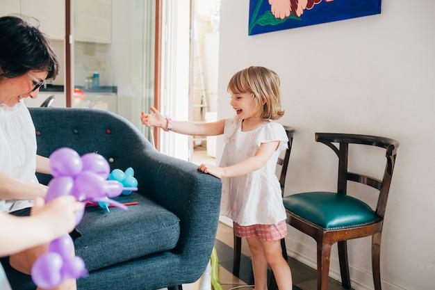 Молодая красивая девочка крытый дома, играя со своей мамой