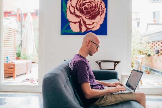 コンピューターを使用して自宅で座っているソファで屋内半ばの成人男性