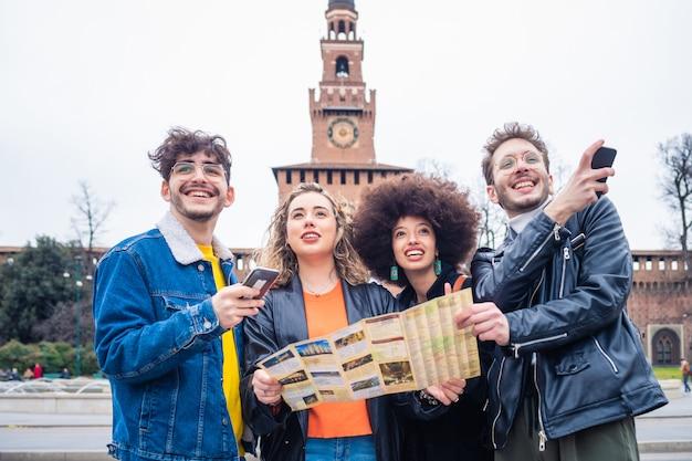 Группа молодых красивых многонациональных друзей туристов на открытом воздухе с использованием карты