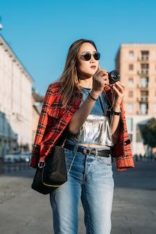 カメラを使用して屋外の街を訪れる若い美しいアジアの女性