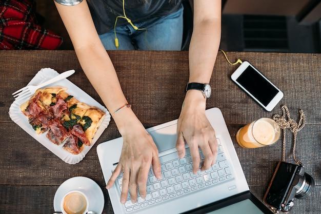 ラップトップコンピューターを使用して俯瞰の女性手