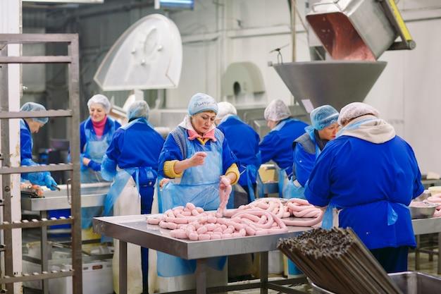 肉工場でソーセージを処理する肉屋。