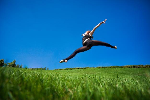 笑顔の若い体操選手が分割でジャンプし、地球の上に浮かんでいます。
