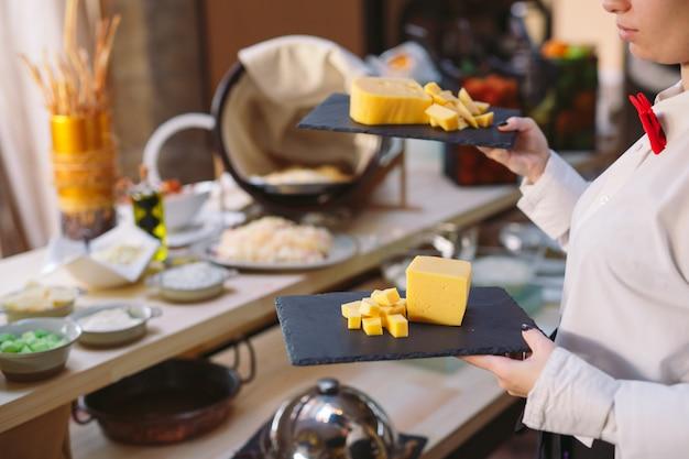 Буфет. официант держит тарелку нарезанного сыра.