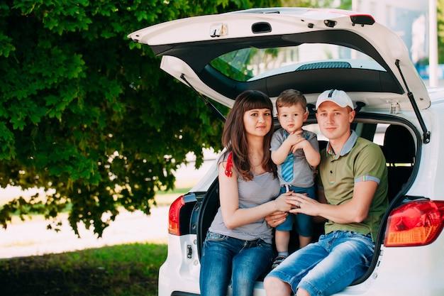 幸せな家族が車の中で座っています。