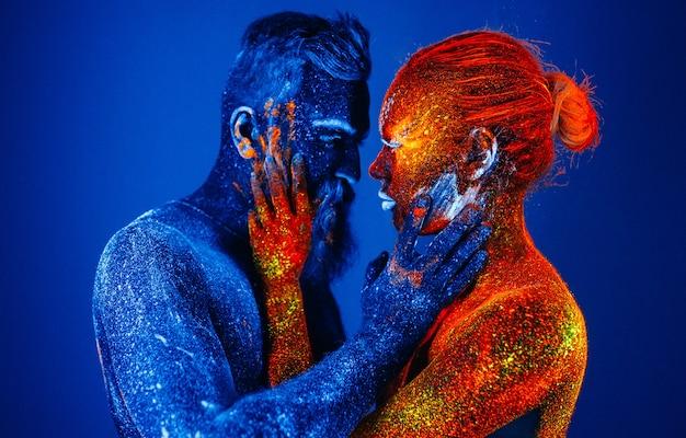 Портрет бородатого мужчины и женщины окрашены в ультрафиолетовую пудру.