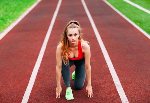 Спортивная (ый) женщина на треке, начиная бежать. концепция здорового фитнеса с активным образом жизни.
