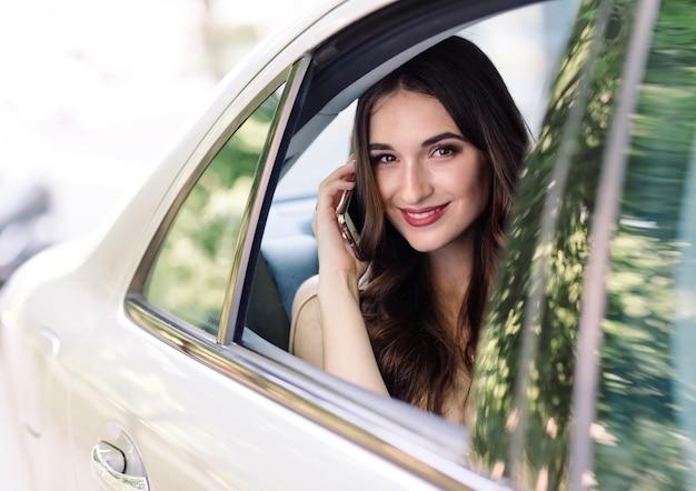 Молодая девушка сидит на заднем сиденье автомобиля и разговаривает по телефону.