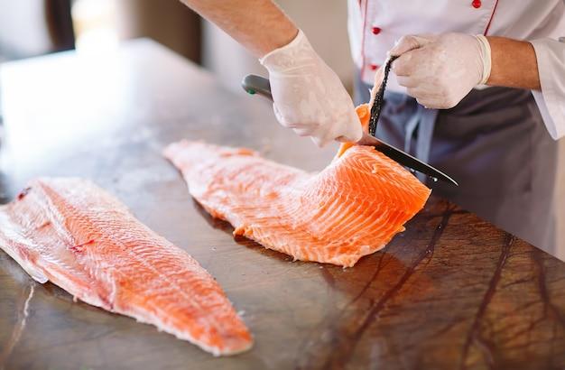 シェフはテーブルの上でサーモンを切ります。