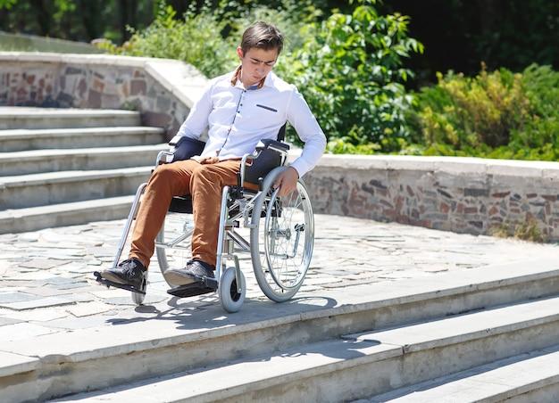 階段を降りることができない車椅子の若者。