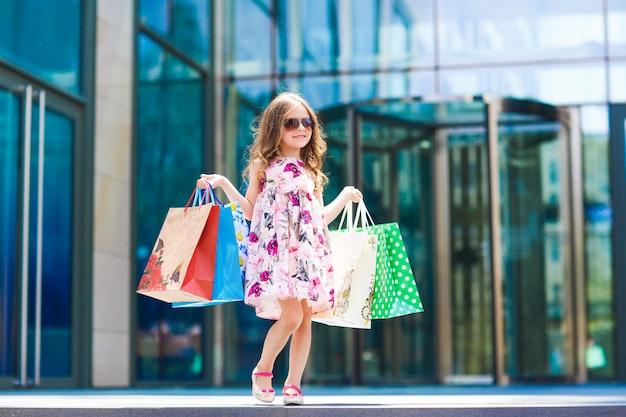 Милая маленькая девочка по магазинам, портрет ребенка с сумками, покупки, девушка.