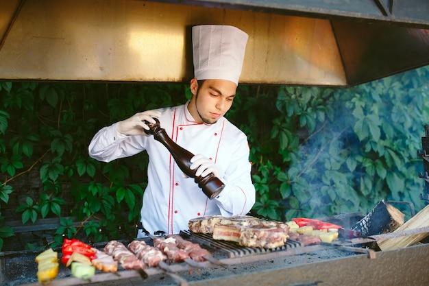 シェフはバーベキューで肉を準備します。