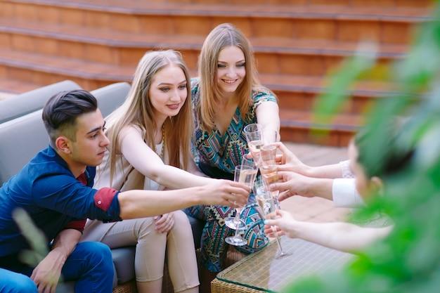 Празднование, люди держат бокалы с шампанским, делая тост