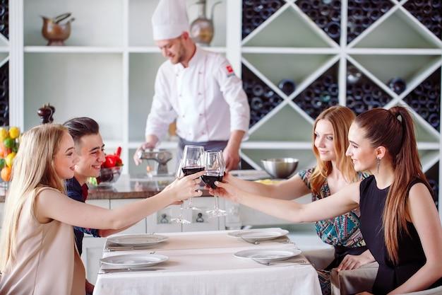 Молодежь в ресторане пьет вино, на заднем плане готовит повар.