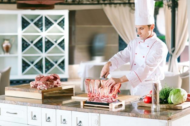 男の料理人がレストランでナイフで肉を切る。