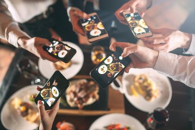 外出して携帯電話と一緒に食べ物の写真を撮る友人のグループ