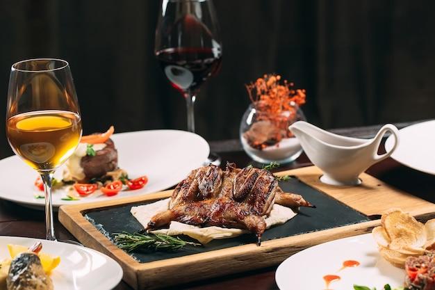 焼きヤマウズラ、スズキ、タルタル。レストランのテーブルの上のさまざまな料理。