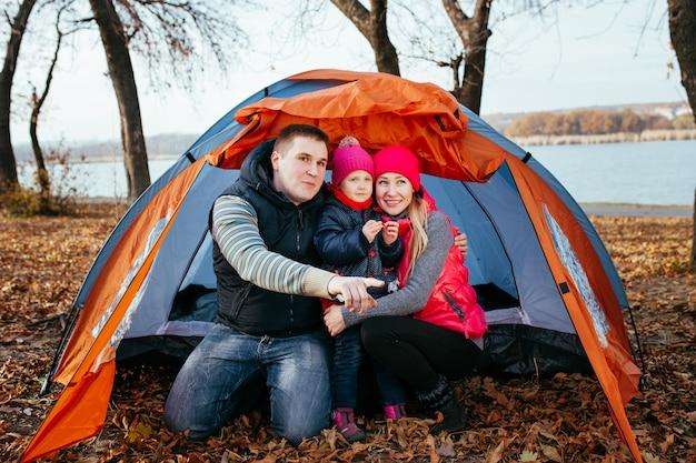 テントキャンプに座ってポーズをとって幸せな家族