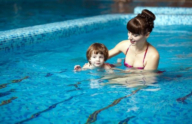 Мама учит ребенка плавать в бассейне