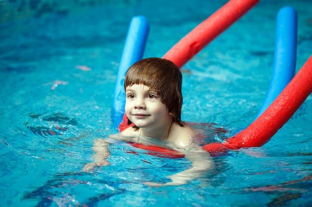 子供がプールで泳ぐ