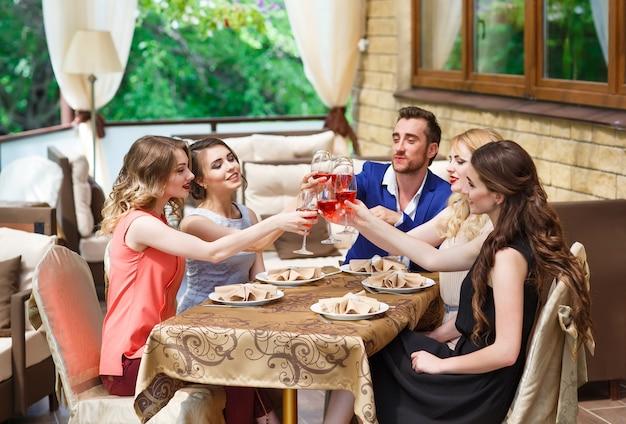 Друзья пьют вино на летней террасе
