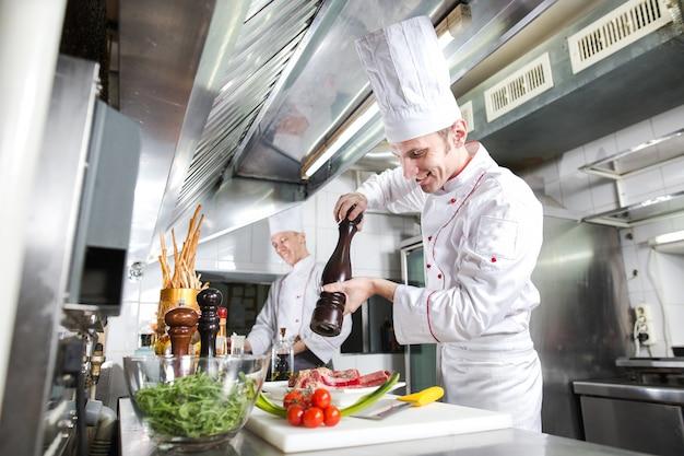 Шеф-повар готовит блюдо на кухне ресторана