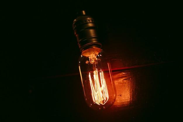 木製の壁にビンテージ白熱エジソン型電球