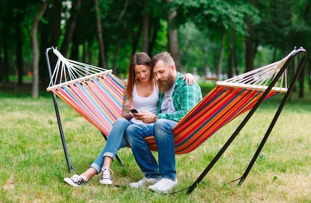 Молодая пара с мобильным телефоном сидит в гамаке