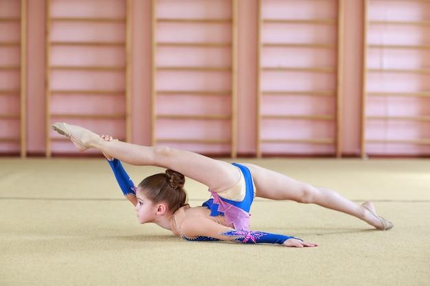 Молодая девушка делает гимнастику.