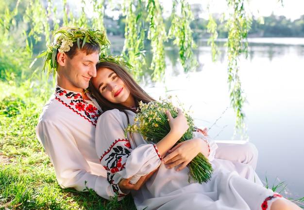 Середина лета. молодая влюбленная пара в славянских костюмах на берегу озера. славянский праздник ивана купалы.