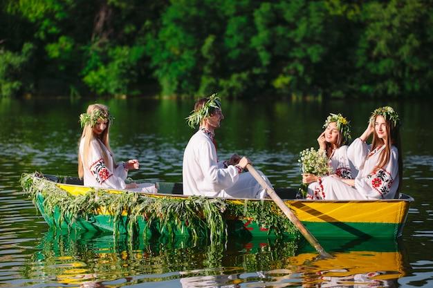 Середина лета. группа молодых людей в национальных костюмах плывет в лодке, украшенной листьями и наростами. славянский праздник ивана купалы.