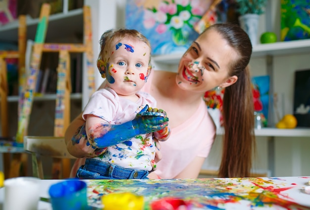 Мама и дочка рисуют на холсте в рисовальной школе.