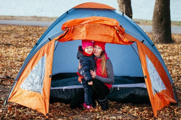 幸せな母と娘がテントに座ってポーズ