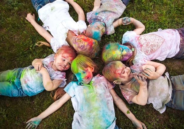 草の上に横たわる子供たちホーリー祭の色に塗られた子供たちは草の上に横たわる