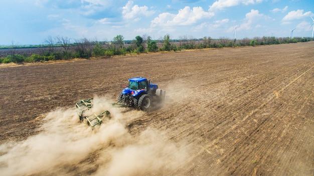 畑で耕し播種するトラクター