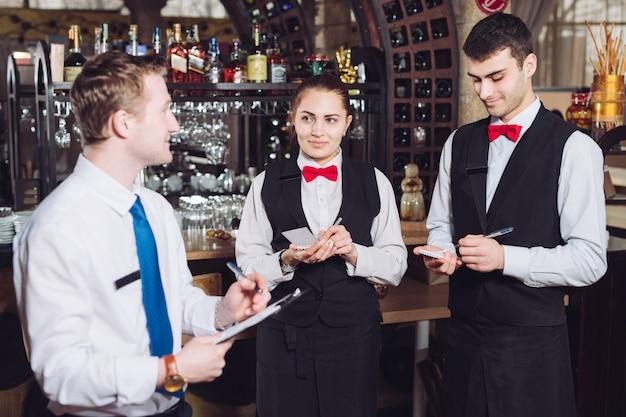 Брифинг менеджера с официантами. менеджер ресторана и его сотрудники.