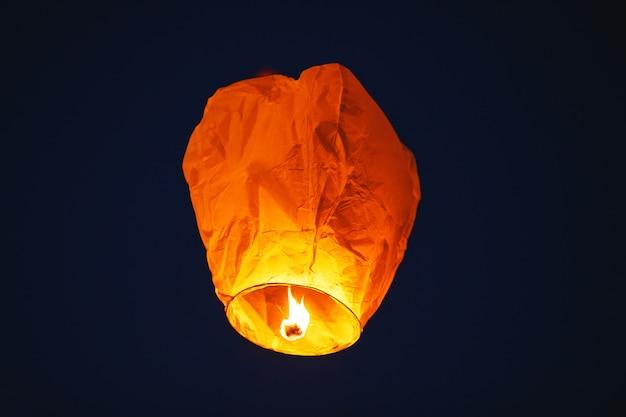 Летающий фонарь в темном небе