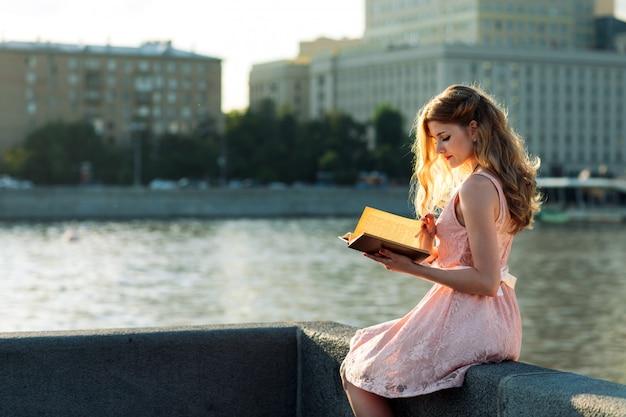 Молодая девушка читает книгу на берегу реки.