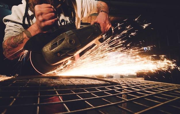 Рабочий, использующий угловую шлифовальную машину на фабрике и бросающий искры