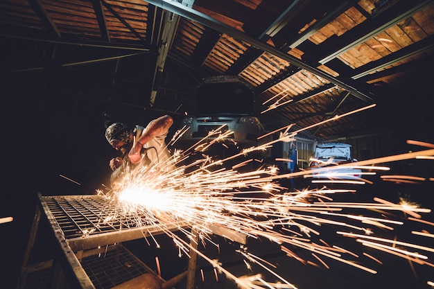 Сотрудник автосервиса производит ремонт кузова со сварочным аппаратом в ручных искрах