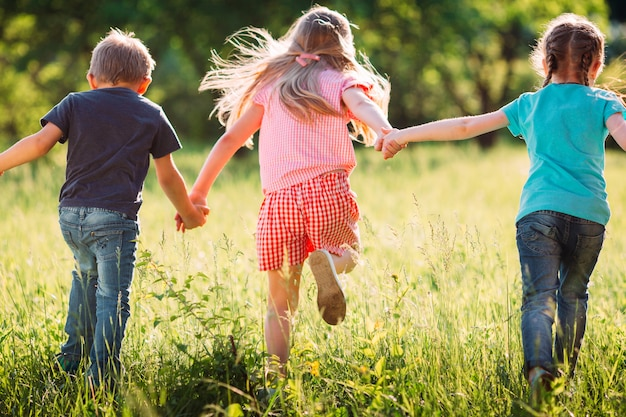 晴れた夏の日に公園でカジュアルな服を着て走っている子供、友人男の子、女の子の大規模なグループ。