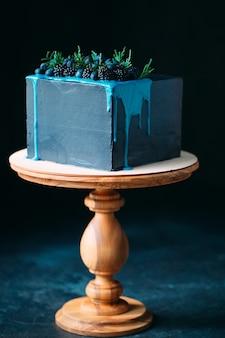 ブラックベリーとブルーベリーで飾られた青いケーキ。