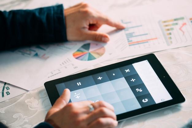 Конец-вверх руки предпринимателя анализируя счет на таблетке цифров над столом.