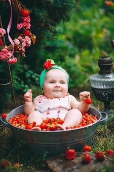 小さな女の子が庭でイチゴを洗面器に浴びます。