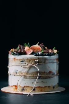 Фруктовый торт, украшенный инжиром, печеньем и черникой.