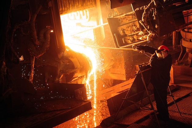 鉄鋼生産のための工場。電気溶解炉。工場労働者が金属のサンプルを採取します。