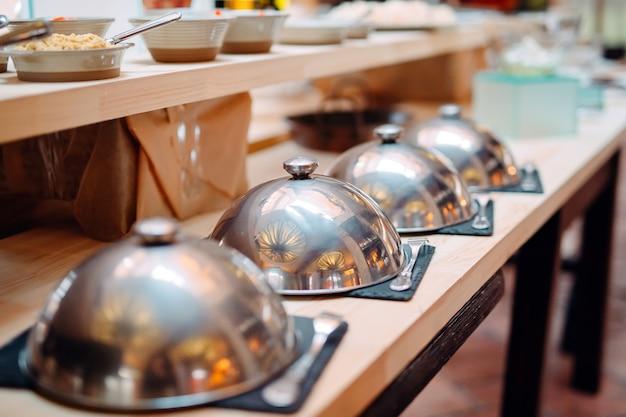 Шведский стол в ресторане или отеле. металлическая посуда с крышками.