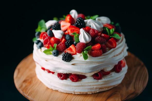 Фруктовый торт торт украшен ягодами на деревянной подставке на черном.